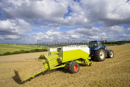 tractor and baler baling straw in