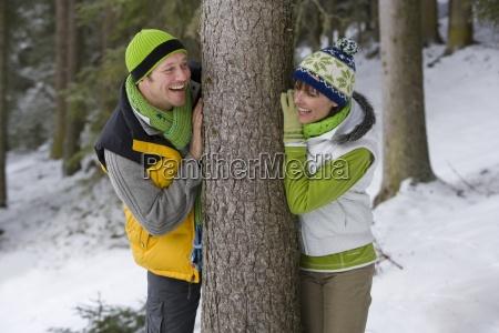 usmiechnieta para oparty o pien drzewa