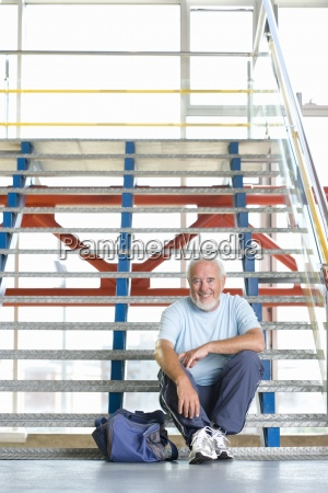 senior man with bag on stairs