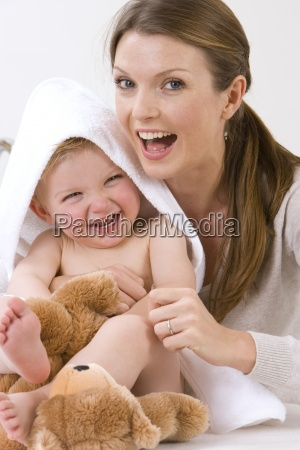 mother hugging laughing baby boy with