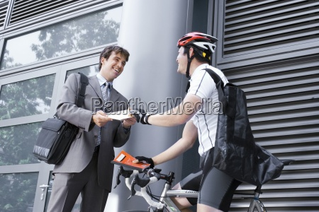 rowerowy kurier dostarcza paczke do biznesmena