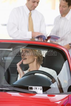 kobieta siedzi w czerwonym kabrioletem w