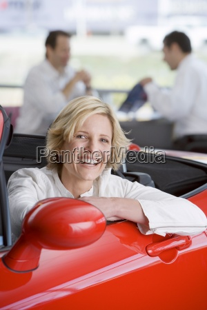 sprzedawca z klientem w salonie samochodowym