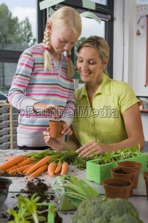 nauczyciel i uczniowie sadzenia warzyw w