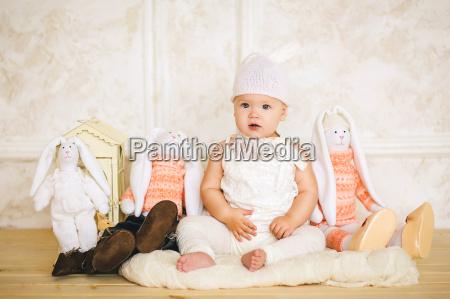 male dziecko w garniturze zajaca siedzi