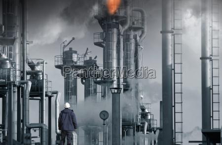 pracownik stoi przed rafinerii ropy naftowej