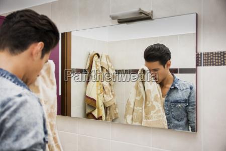 odbicie czlowieka suszenia twarzy z recznikiem