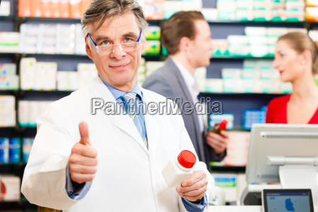 pharmacist in his pharmacy with customers