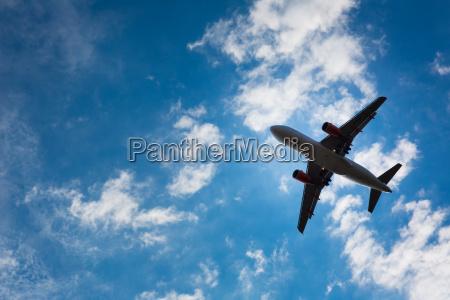ciemna sylwetka samolotu lecacy nad blekitnym