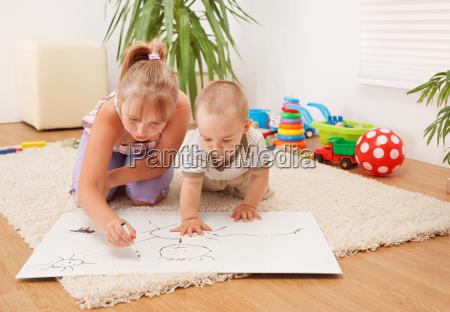 dzieci rysujac w pokoju