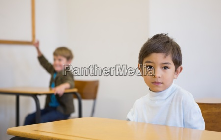 uczen patrzac na kamery na biurku