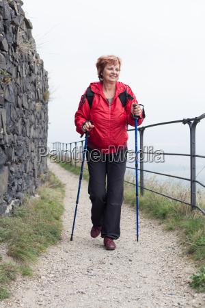 starsza kobieta nordic walking na skalistym