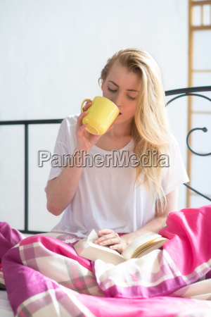 girl sitting in bed with book