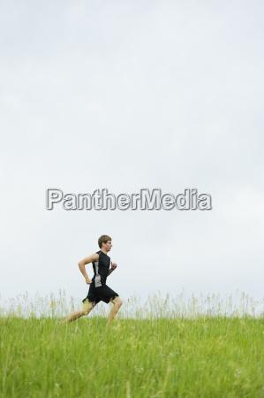 mlody czlowiek dziala na szlaku trawy