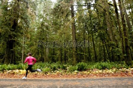 kobieta jogging w dol drogi obok