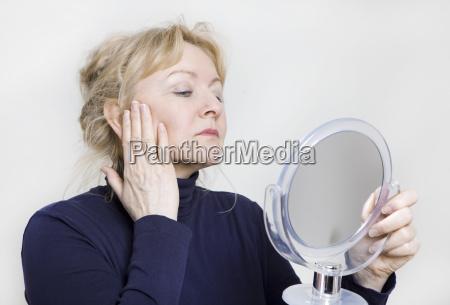 starsza kobieta patrzy w lustro
