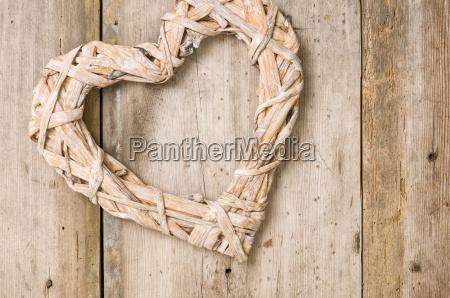 plecione serce przed rustykalnymi drewnianymi deskami