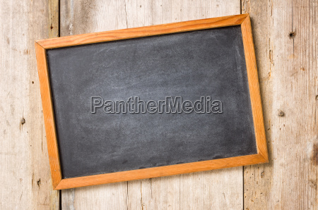 pusty blackboard przed nieociosanym drewnianym tlem