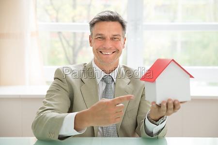 happy businessman holding house model