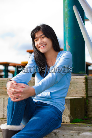 young teen girl sitting on wooden