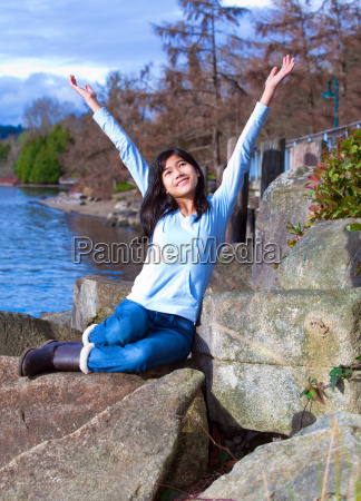 young teen girl arms raised while