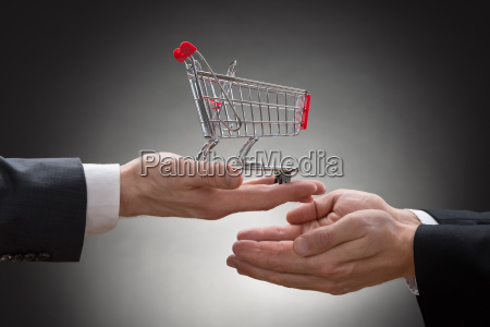 businesspeople hands with shopping cart