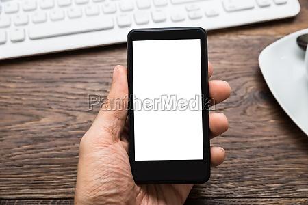 osoby trzymajacej telefon komorkowy na biurku