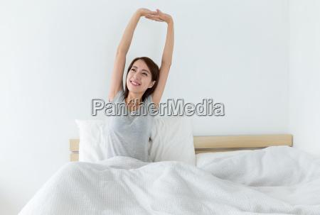 mloda kobieta budzi sie szczesliwie po