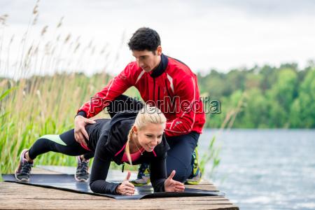 kobieta robi pompki osoba trenera fitnessu