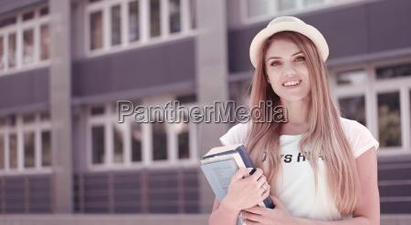 pretty student z ksiazek na uniwersytecie