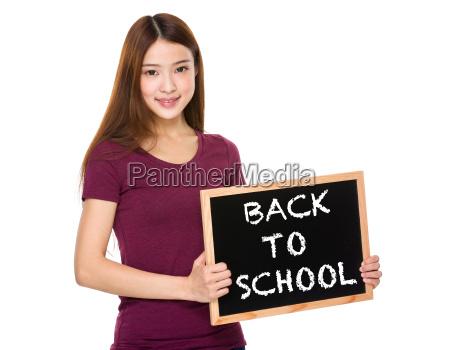 mlody uczen trzymac z tablica pokazujac