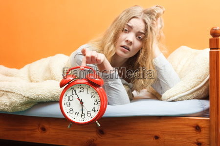 unhappy woman waking up with alarm