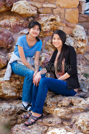 two young teen girls sitting together