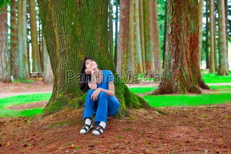 young teen girl sitting under large
