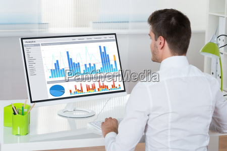 businessman analyzing graphs on computer