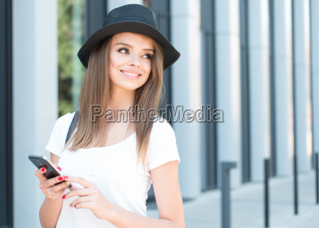 pretty girl holding phone outside the