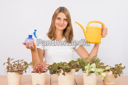 dziewczyna trzyma butelke natrysku i podlewania