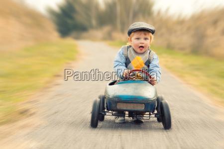 usmiechniety chlopiec z jego pedal samochodowy