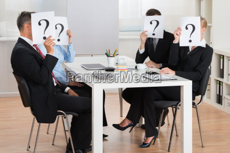 businesspeople hiding faces behind question mark