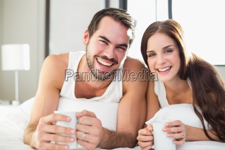 young couple having coffee in bed
