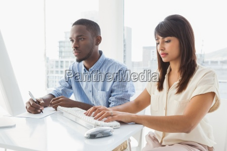 concentrated teamwork using computer and taking