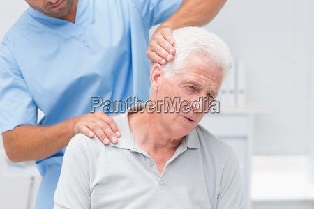 physiotherapist giving physical therapy to senior