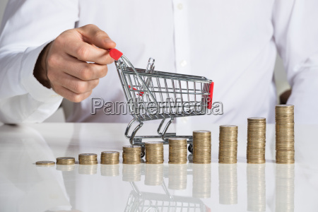 businessman holding shopping cart by stacked