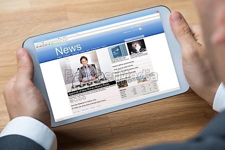 biznesmen czytanie nowiny u cyfrowy tabliczka