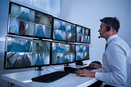 operator systemu bezpieczenstwa patrzac na nagrania