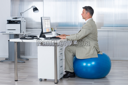 businessman using computer while sitting on