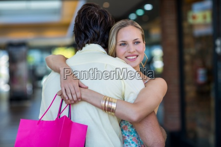 smiling woman with shopping bags hugging