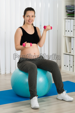 pregnant woman doing exercise on fitness
