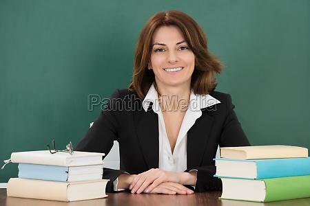 kobieta nauczyciel siedzi w klasie biurko
