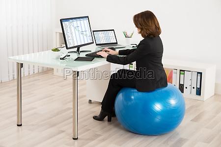 businesswoman sitting on pilates ball working